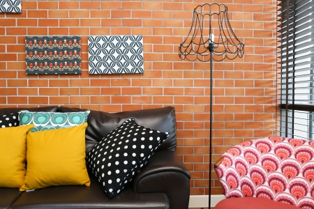 Colorful pillows on a sofa with brick wall in background photo