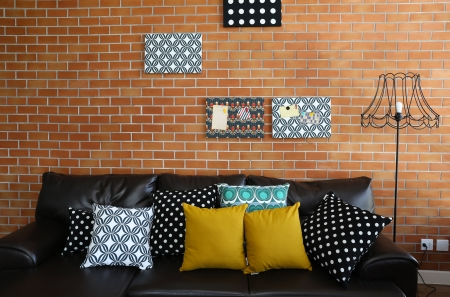home furnishing: Colorful pillows on a sofa with brick wall in background Stock Photo