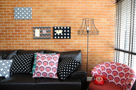 furnished: Colorful pillows on a sofa with brick wall in background Stock Photo