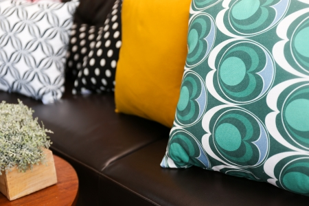 Close-up of colorful pillows on a leather sofa