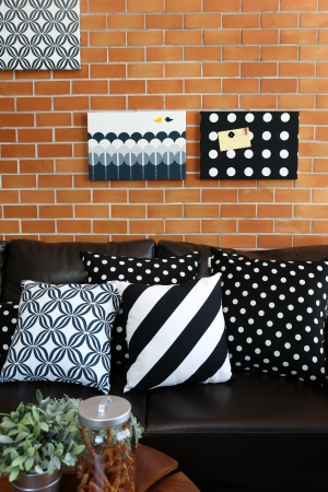 Pillows on a sofa with brick wall in background Stock Photo