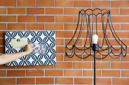 Hands putting magnet memo on pattern cardboard with vintage lamp and brick wall background