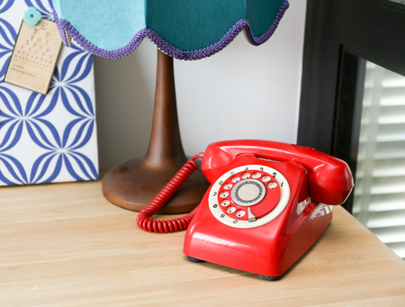 Red vintage telephone with rotary on wooden desk Archivio Fotografico