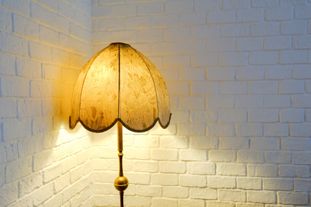 Lit up vintage lamp with white brick wall background