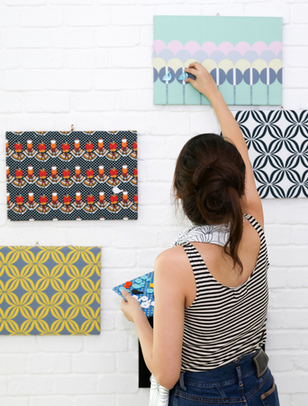Asian girl decorate her home with magnets and pattern on white brick wall background Archivio Fotografico