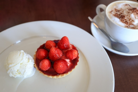 Strawberry tart and vanilla ice cream with a cup of coffee in background photo