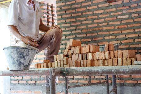 Worker and stacks of brick ready to build house wall in a construction site Archivio Fotografico