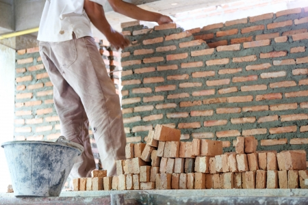 Worker laying bricks to build house wall in a construction site Archivio Fotografico