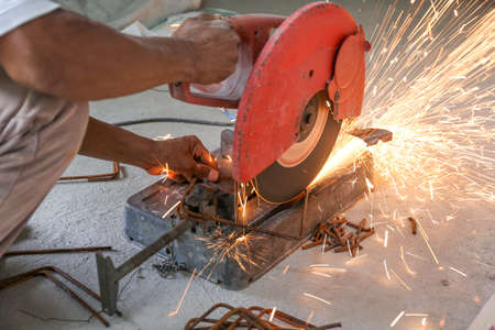 Worker cutting metal with cutter for house construction Archivio Fotografico