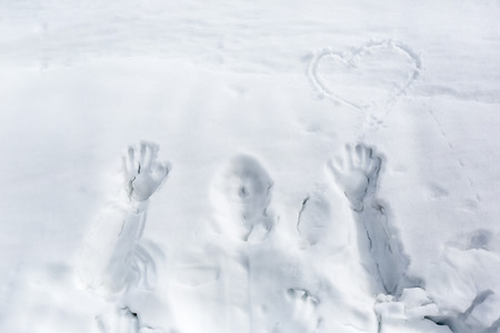 Sign of a heart and man on snow surface