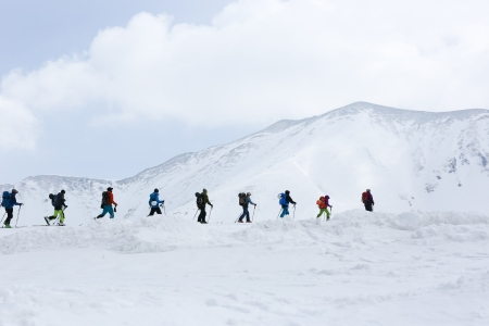 Group of snowboarders climbing to mountain top to start snowboarding