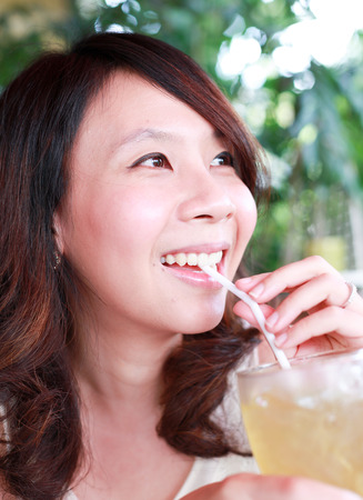 Happy asian girl drinking juice and smiling Archivio Fotografico