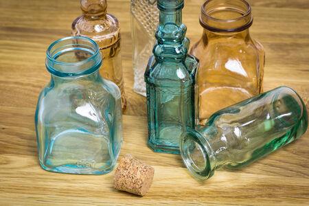 botellas vacias: Colección de botellas de vidrio de época vacías en una mesa de madera
