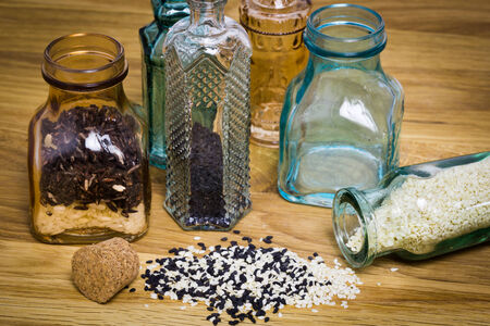 Sesami seed and rice in glass bottles on wooden table