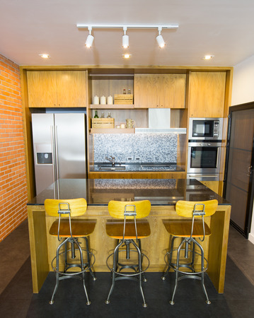 Stylish modern contemporary kitchen with island bar, chair and home appliances photo