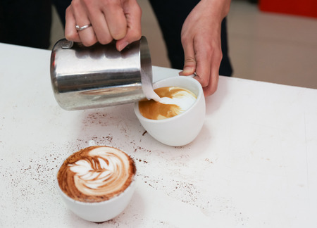 Barista making a cup of beautiful latte art coffee