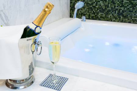 Champagne glass and Jacuzzi Spa with colourful light whirlpool Stock Photo