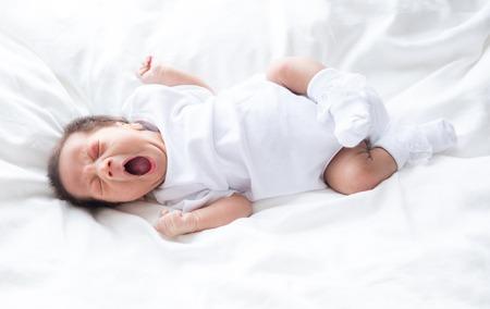 Asian infant baby lying on white bed background Stock Photo