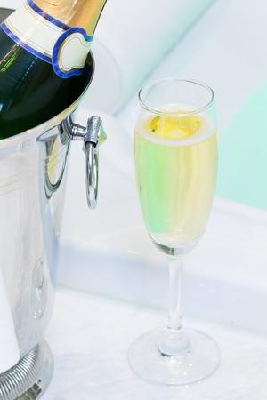 Champagne glass and bath tub Spa with colourful light whirlpool Archivio Fotografico