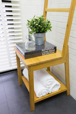 Interior decoration of modern contemporary toilet with wooden chair, books, and towel