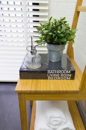 Decorazione interna della moderna gabinetto contemporanea con la sedia in legno, libri, e asciugamano Archivio Fotografico - 34553778
