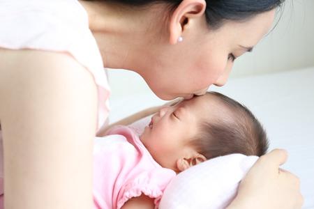 madre y bebe: Asia madre jugando con su bebé recién nacido acostado en el fondo cama blanca