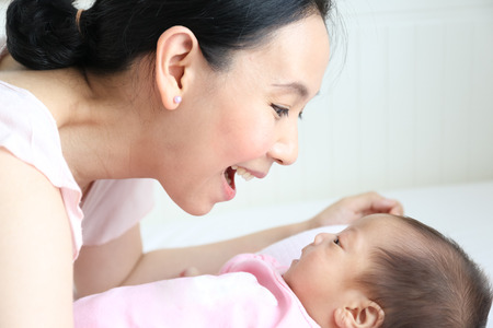 Asian mother playing with her infant baby lying on white bed background