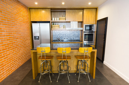 Stylish modern contemporary kitchen with island bar, chair and home appliances