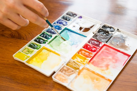 paint palette: Paintbrush and paint palette with artists hand holding brush painting colorful mixed watercolor