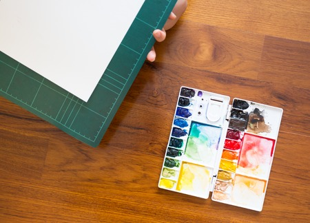 Paintbrush and paint palette with colorful mixed watercolor Archivio Fotografico