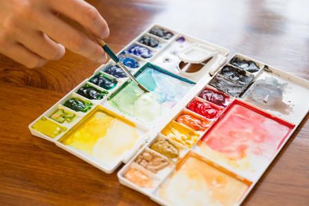 Pennello e vernice tavolozza con tenendo artisti mano pennello pittura acquerello colorato misto Archivio Fotografico - 36483546
