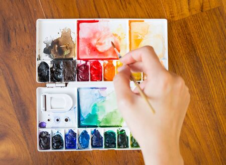 Paintbrush and paint palette with artists hand holding brush painting colorful mixed watercolor