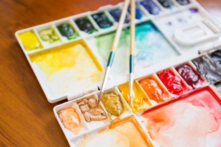 Paintbrush and paint palette with colorful mixed watercolor Stock Photo