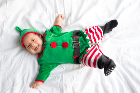 Baby in green elf costume for christmas holiday on white background