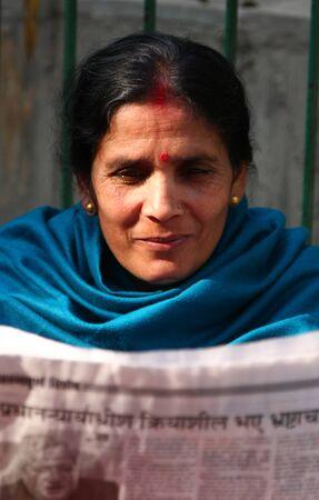 KATHMANDU, NEPAL-DECEMBER, 2009 - An unidentified nepalese woman reading newspaper in the morning near by the street