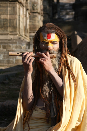 ascetic: KATHMANDU, NEPAL-DECEMBER, 2009 - An unidentified ascetic or sadhu in pashupatinath temple waiting for travellers to take pictures in exchange with some money