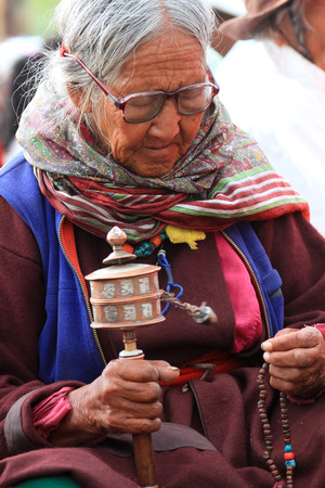 LEH, INDIA-MAY, 2012 - An unidentified tibetan old woman praying in a meeting session with his holiness the dala lama in summer Editorial