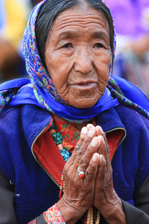 LEH, INDIA-MAY, 2012 - An unidentified tibetan old woman praying in a meeting session with his holiness the dala lama in summer Editoriali