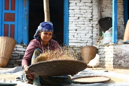 KATHMANDU, NEPAL-DICEMBRE 2009 - Una donna nepalese non identificata che fa il proprio dovere quotidiano lungo la strada in estate Archivio Fotografico - 38952671