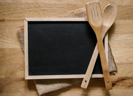 Blackboard on wooden surface and serving spoons with napkin, cooking concept