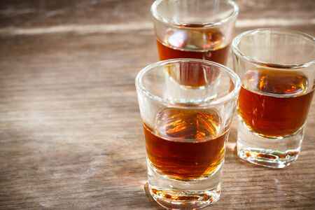 shooter drink: Glass of whiskey on wooden background close up