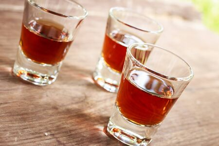 shooter drink: glass of whiskey put on old wooden backgound