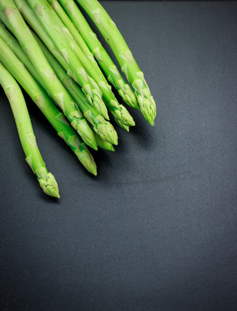 black background: organic asparagus with blackboard image of food background