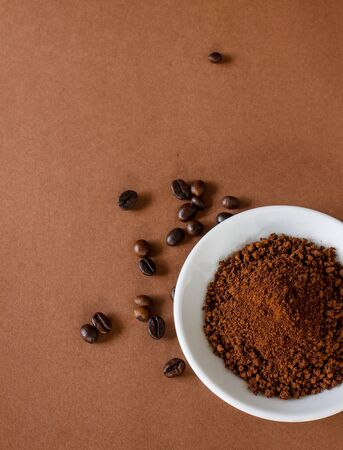 small plate: Coffee in white small plate put on brown paper background , texture and text