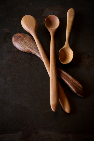 wooden spoon: old wooden cooking spoon on grunge background, still life image dark tone