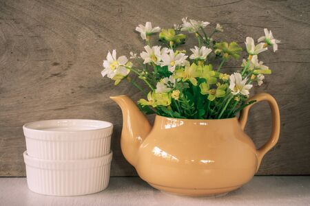 yellow tea pot: Flower in a yellow tea pot and two white cup on wooden background, cozy home rustic decor, cottage living Stock Photo
