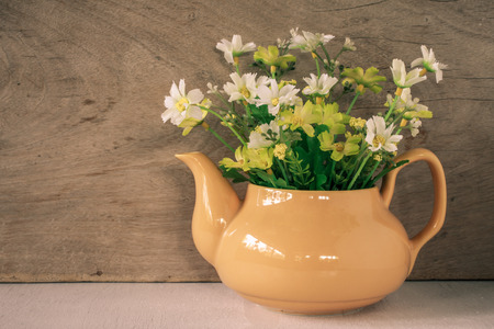 yellow tea pot: Flower in a yellow tea pot on wooden background, cozy home rustic decor, cottage living