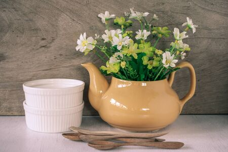 yellow tea pot: Flower in a yellow tea pot and two white cup and wood spoon on wooden background, cozy home rustic decor, cottage living
