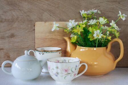 yellow tea pot: Flower in a yellow tea pot and vintage cup of coffee on wooden background, cozy home rustic decor, cottage living