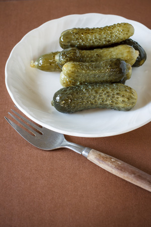gherkins: Pickled Gherkins serve in white plate with brown paper background Stock Photo